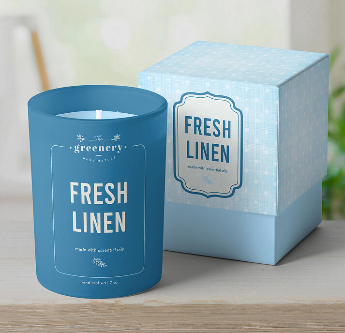 Branded open candle jar next to cardboard packaging box