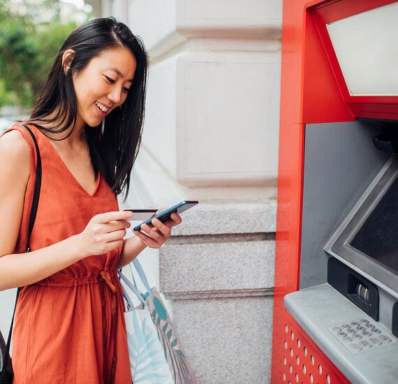 woman using ATM successfully accesses all her financial and banking information through mobile app