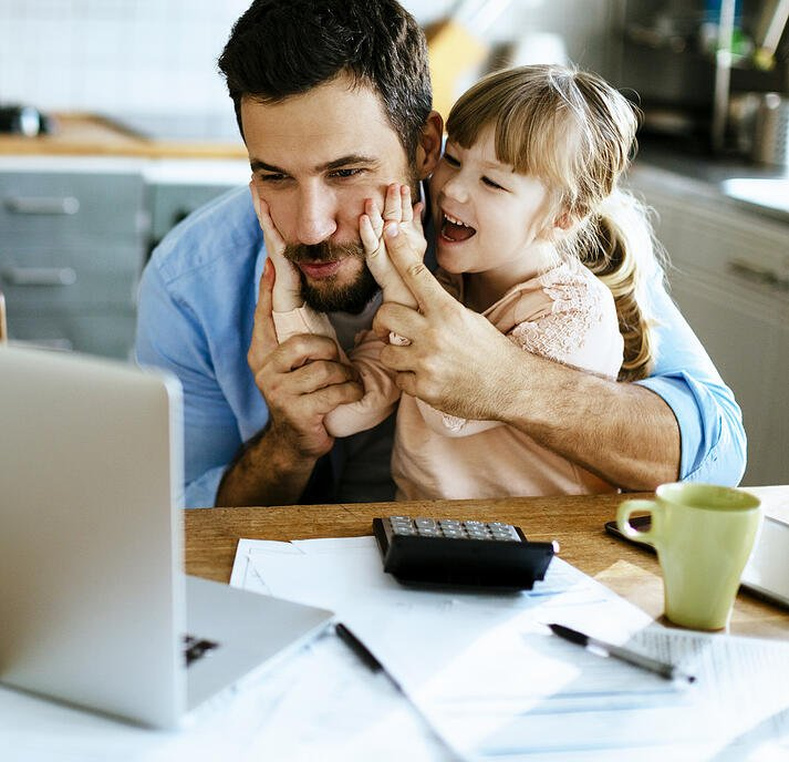 dad and young daughter sitting at kitchen table looking at insurance statement on laptop